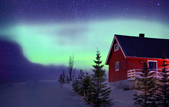 A red house in Tromso, Norway with the Aurora Borealis in the sky