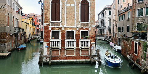 A brown stone building in the middle of the Venice canals.