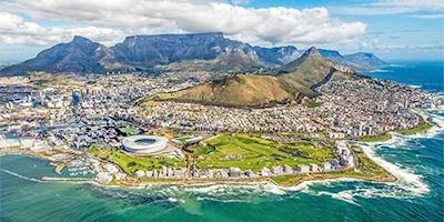 Aerial shot of the city of Capetown with water in front and mountains in back.