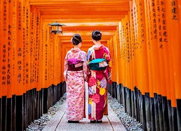 Geisha women standing near Torii Gate in Kyoto, Japan