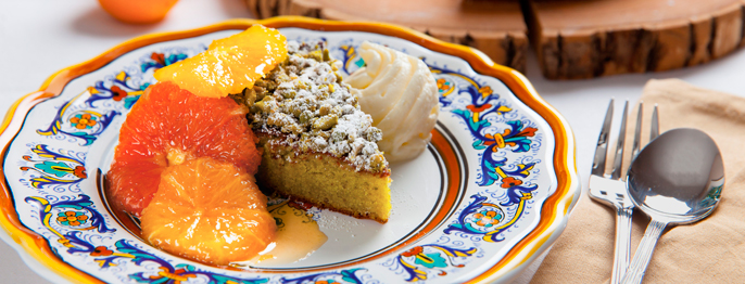 Pistachio Torta - a mildly green cake covered in bright citrus wheels, served on a decorative platter.