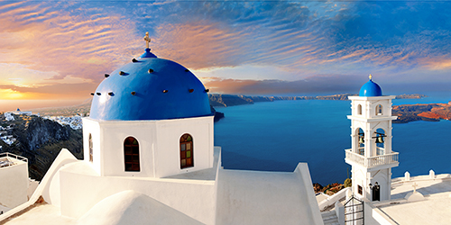 A pink tinged sunset over blue domed buildings in Santorini, Greece.