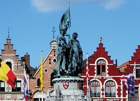 Statue by rooftops in Bruges