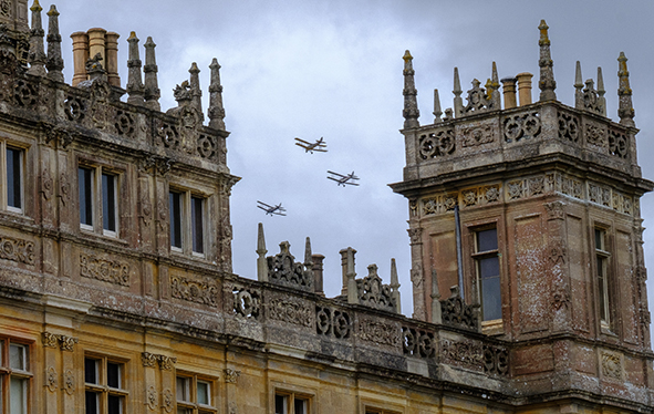 Antique aircraft flying over Highclere Castle, England