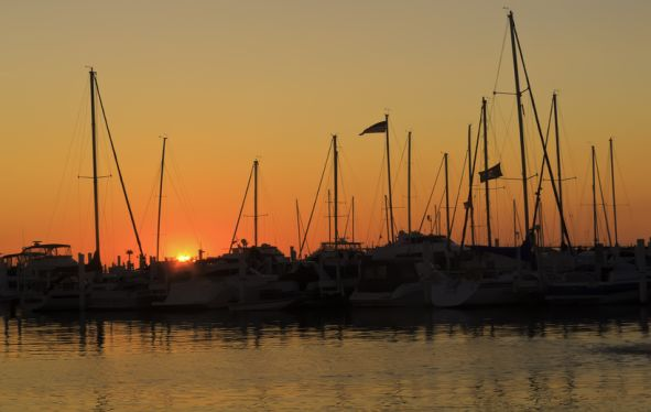 Silhouette of boats with tall masts in front of a setting sunset of orange and grey.