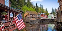 Waterfront buildings in Ketchikan, with an American flag hanging over the water.