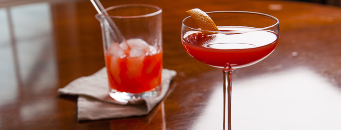 A sicilan negroni, a red liquid in a stemmed glass with a orange peel. Behind is a mixing glass with ice and more red liquid.