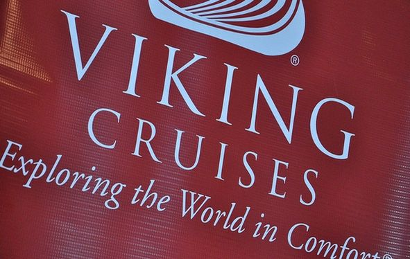 A photo of the Viking Logo in white on a red textured fabric. Viking Cruises Exploring the World in Comfort.