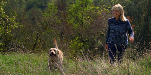 Karine Hagen and her dog, Finse, walking through a field.