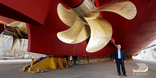 Tor Hagen standing underneath a gold rotar on a Viking Ocean Ship being built.